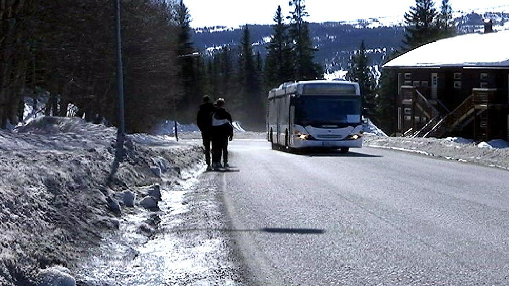 Två person tvingas gå längs bilväg eftersom det saknas gångväg, möter buss.