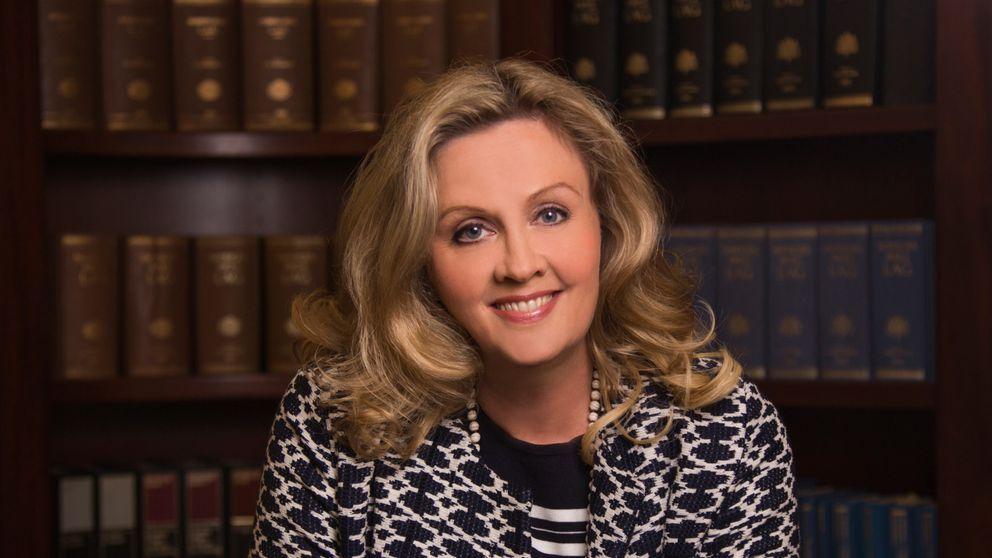 Advokaten Charlotte Nordström framför en bokhylla med lagböcker.
