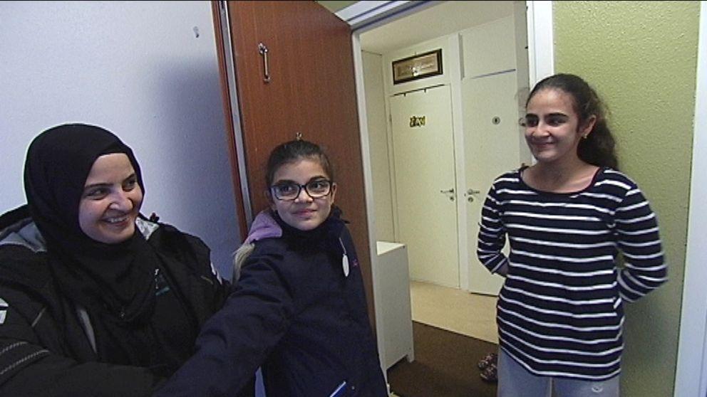Esma Aksungur står i trappuppgång utanför sin öppna dörr, döttrarna ler stolt emot henne.