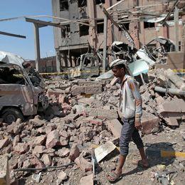 En man går bland ruiner och bråte.