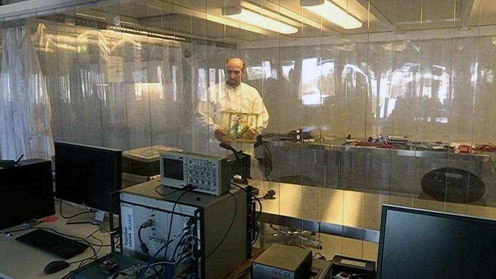 En man bär på ett föremål inne i ett laboratorium.