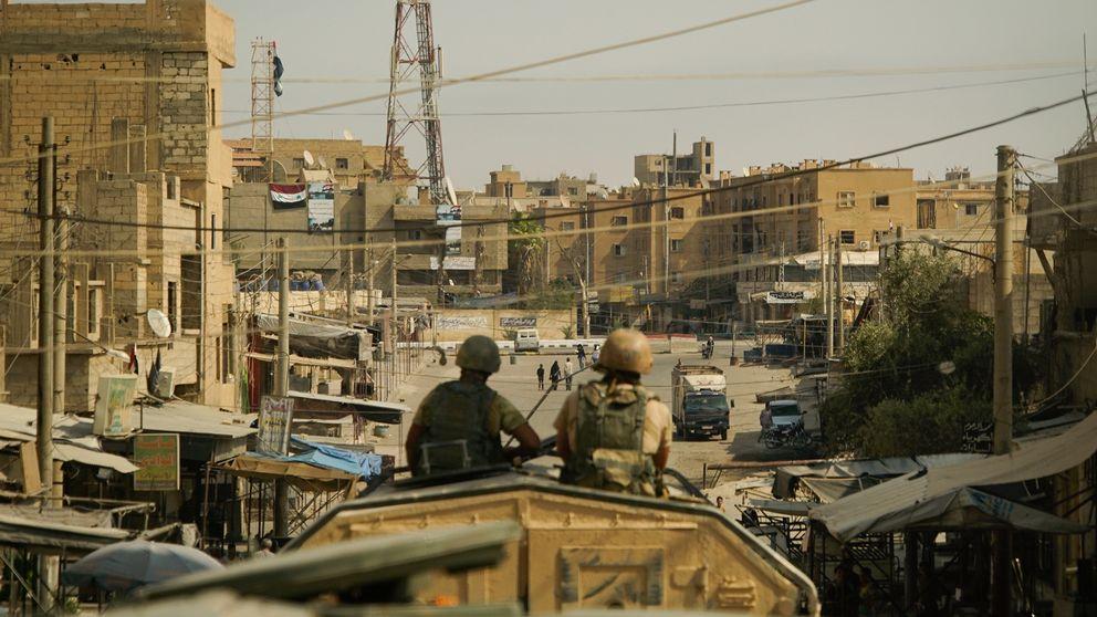 Två män i en stridsvagn blickar ned längs en gata med sandfärgade hus i syriska Deir Ezzor.