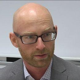 en man med glasögon i kostym