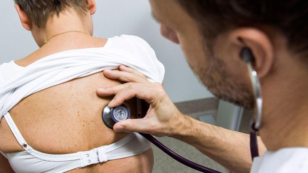 Manlig läkare undersöker kvinna med stetoskop. Arkivbild.