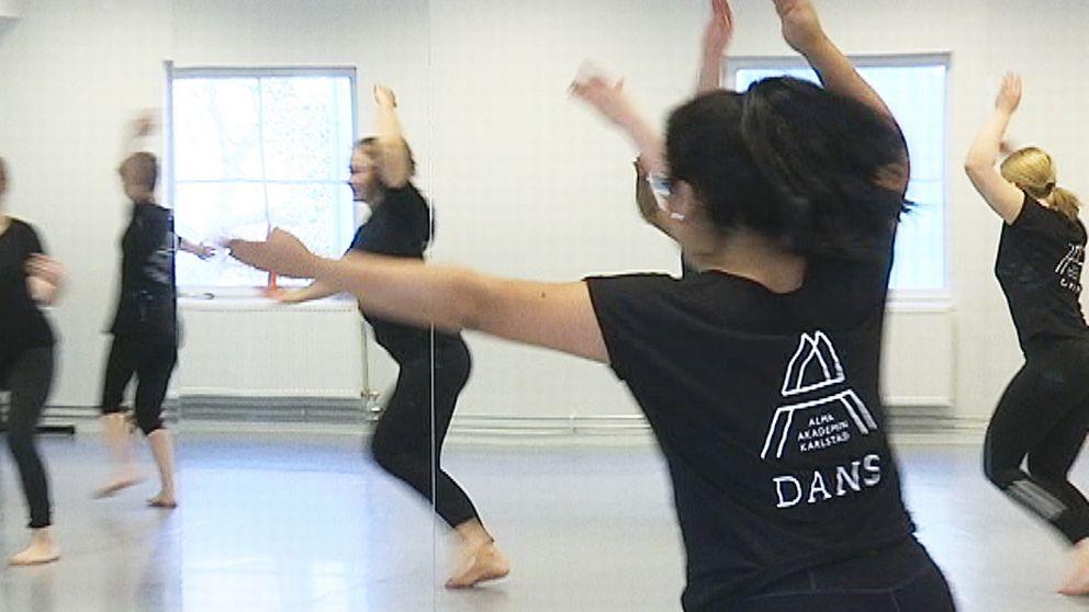Fem ungdomar dansar iklädda svarta kläder. På personen i förgrunden syns AlmaAkademins logotyp på ryggen.