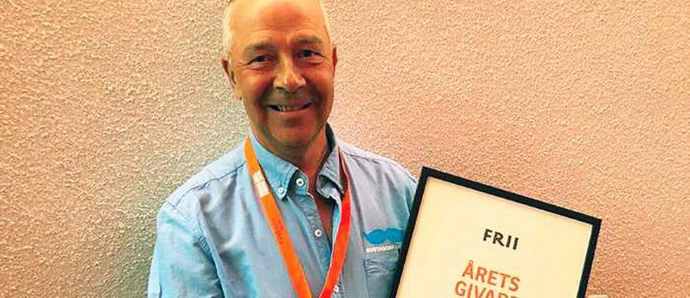 """Håkan Florin står framför en vägg och håller upp ett diplom. På diplomet står """"Årets givare 2017"""". Håkan ler och ser glad ut."""
