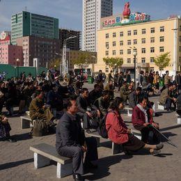 Invånare i Pyongyang i Nordkorea sitter på ett torg och ser på en utsändning från statstelevisionen.