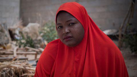 En kvinna i röd slöja och ärr i ansiktet.