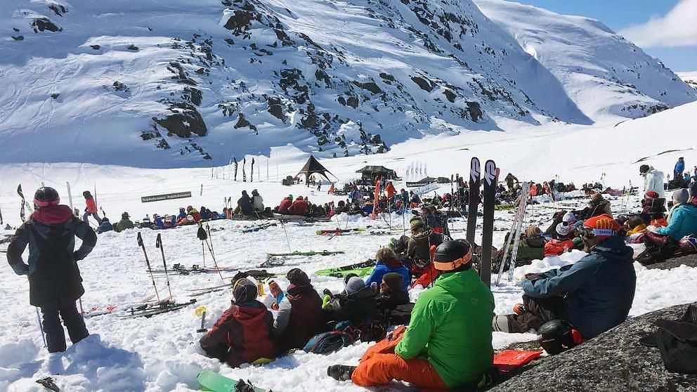 publik sitter i snön nära foten av berg