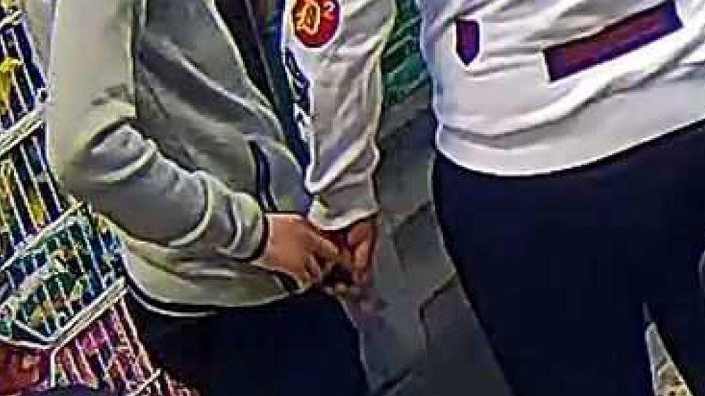 bild från övervakningskamera som visar hur ett pistolliknande föremål lämnas över mellan två personer.