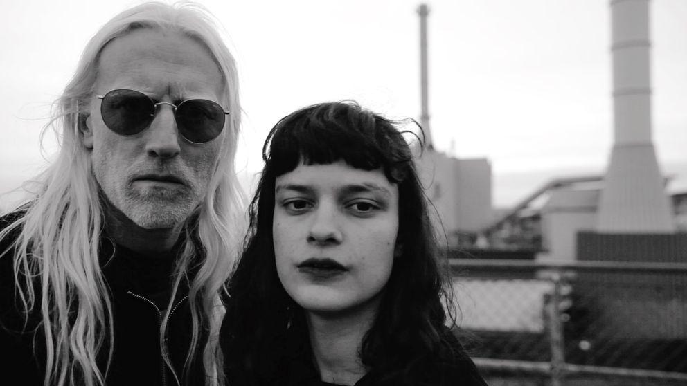 svartvit bild med en blond långhårig man med solglasögon och en mörkhårig kvinna med lugg och värmeverket vid Esperantoplatsen i bakgrunden