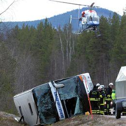 En buss ligger på sidan i diket. En helikopter hovrar över platsen där räddningspersonal jobbar.