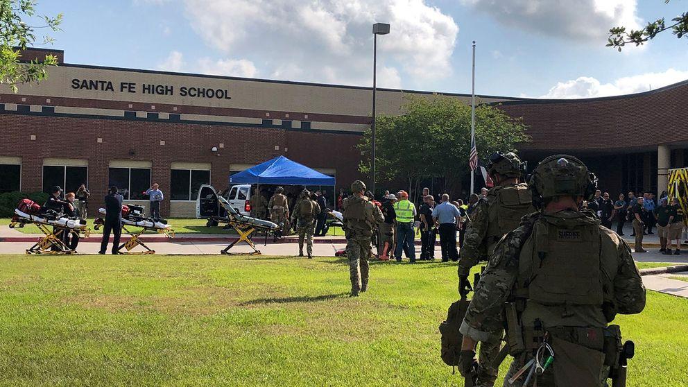 Polisstyrkor på väg in i skolan i Santa Fe under insatsen.