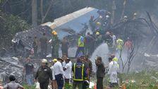 Räddningsarbetare på plats kring det förolyckade planet.