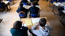 Elever sitter vid skolbänkar i ett klasskrum.