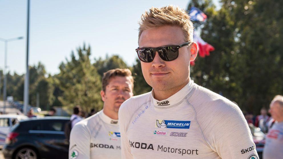Pontus Tidemand står framför träd. Han har en vit tröja med sponsorloggor på och bär mörka solglasögon. Han ler. I bakgrunden skymtar två andra män och några bilar.