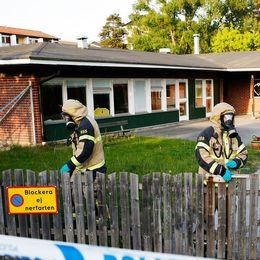 Två personer i skyddsdräkter på förskoleområde.