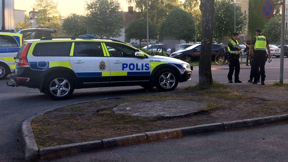 Poliser står vid en polisbil med avspärrningsband i handen.