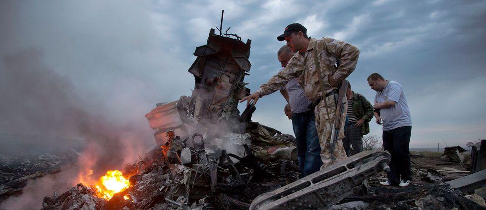 Människor undersöker vraket från planet MH17 i Ukraina i juli 2014.
