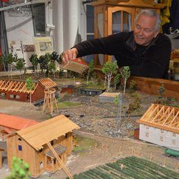 Hans Harnisch lyfter på taket till ett av husen i modellen av gruvfältet i Kaveltorp i Kopparberg.