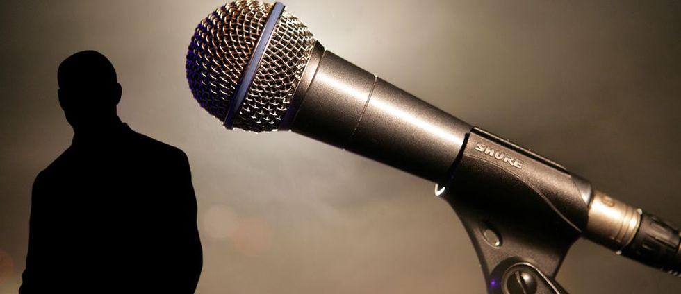 En silhuett av en man tillsammans med en mikrofon.