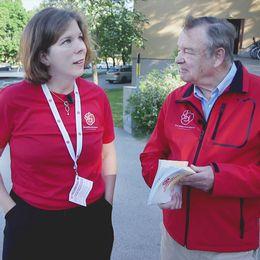 Lars-Olof Blixt och Catharina Piazzolla har på sig röda överdelar med partiets logga, Blixt håller i broschyrer. Till höger: Statsminister Stefan Löfven i kostym med röd slips.
