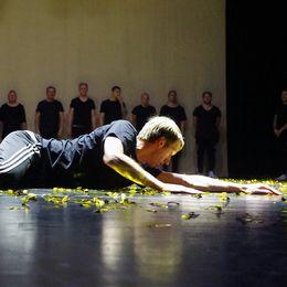 Graham Potter ligger på ett scengolv med guldkonfetti omkring sig.