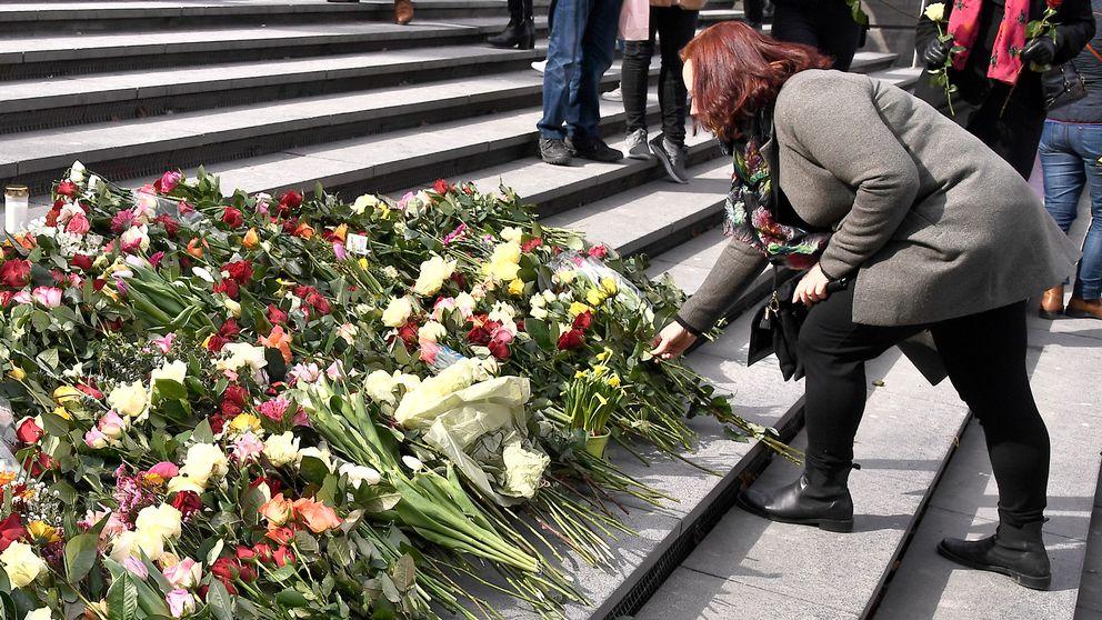Kvinna lämnar blommor på en blomhög.