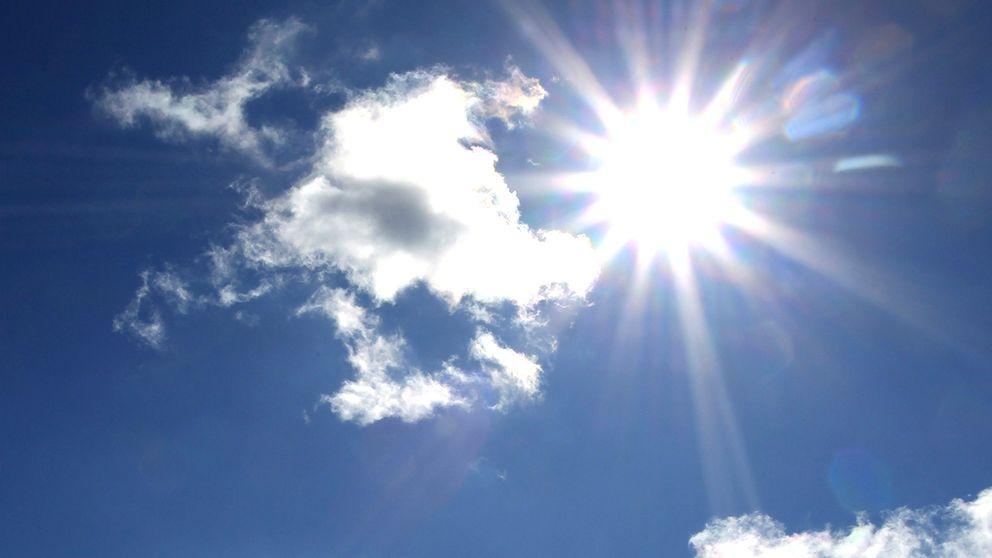 Sol och moln på en blå himmel