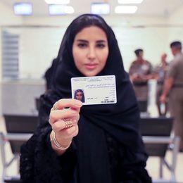 En kvinna håller upp sitt saudiska körkort.