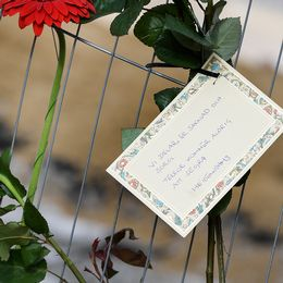 """Blommor och ett kort med texten """"Vi delar er saknad och sorg. Terror kommer aldrig att segra. Heidenstams"""""""