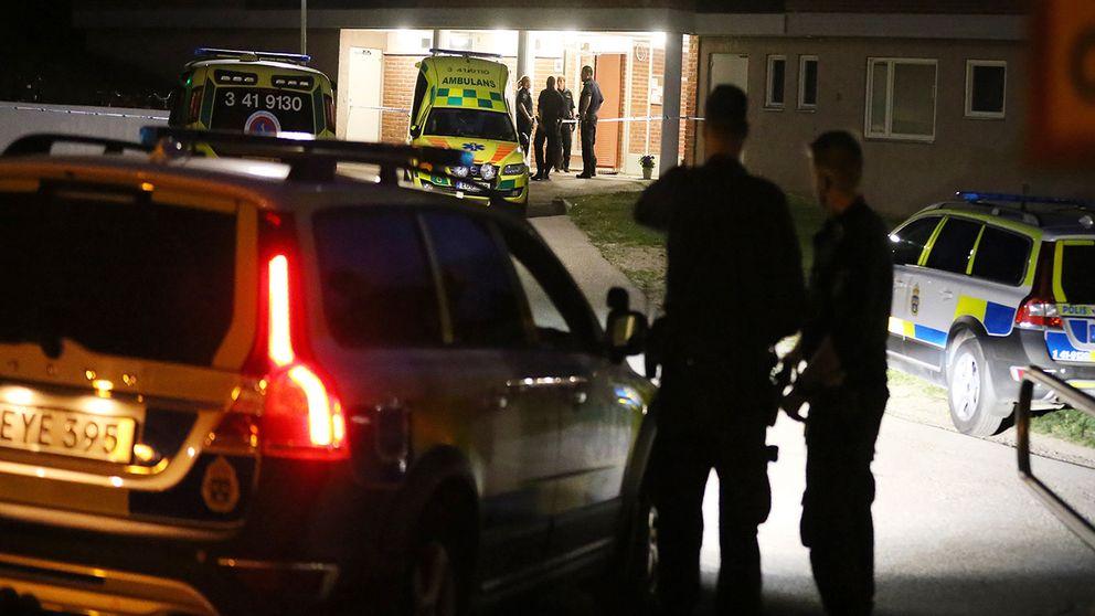 Polisbil och poliser utanför ett flerfamiljshus.