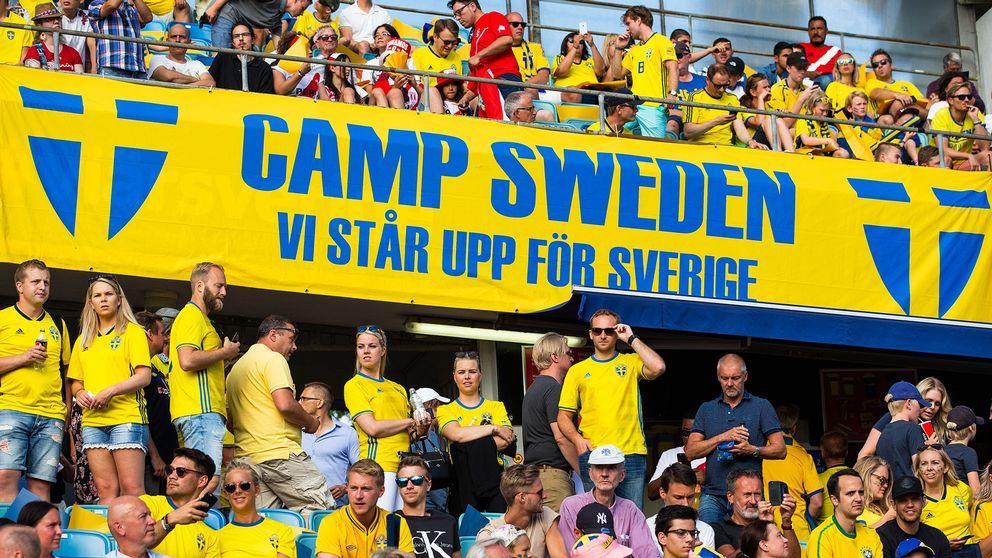 Fullt med fans klädda i svenska gulblå matchtröjor på en fotbollsläktare.