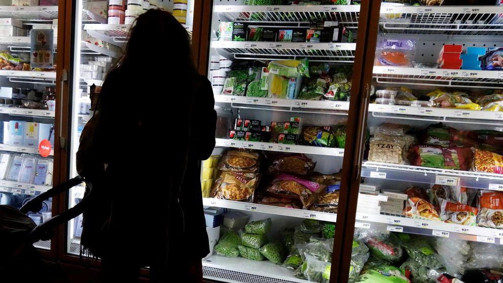 kvinna som står och tittar i frysdisk-hyllor