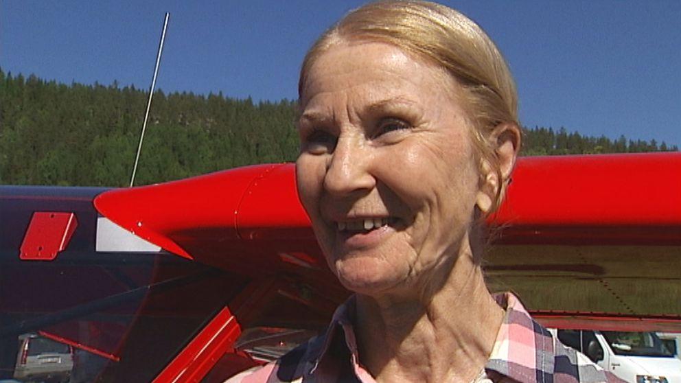 en leende äldre kvinna står ute i solen vid en flygplansvinge