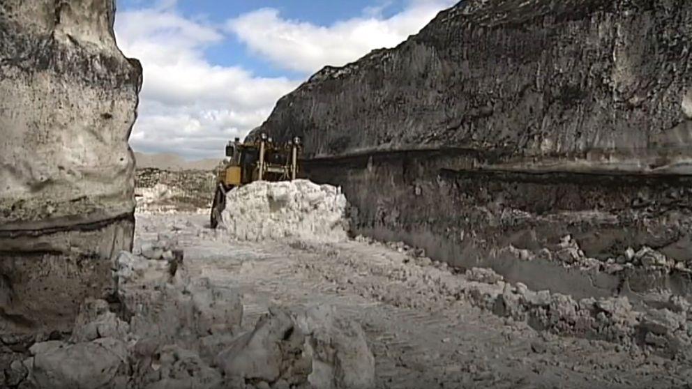 En schaktmaskin forslar bort grå, smutsig snö.