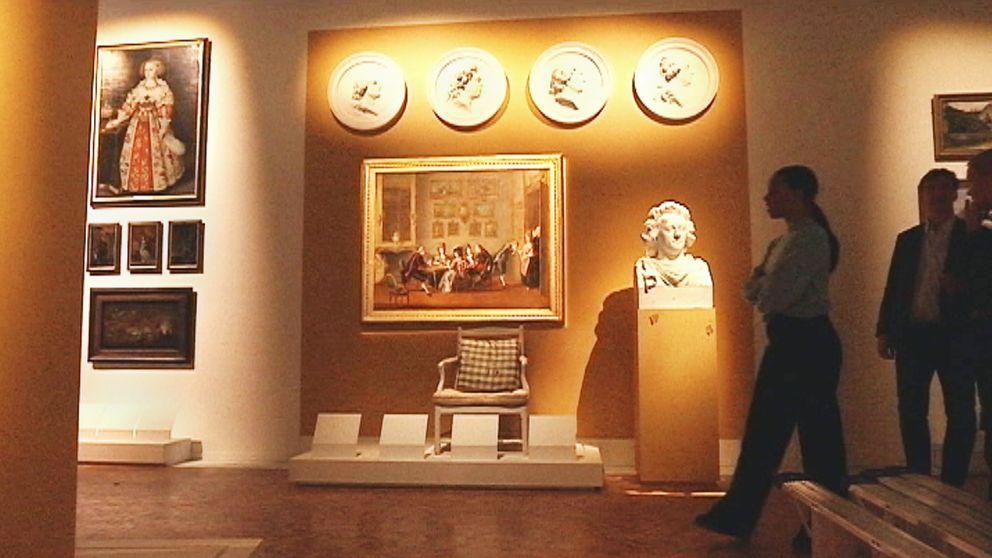 interiör från museum – tavlor, en byst, några personer som går förbi