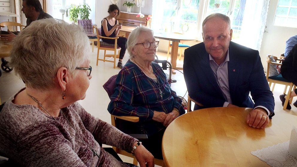 Jonas Sjöstedt sitter tillsammans med två äldre damer vid ett runt bord.