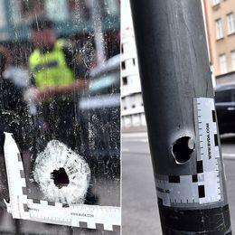 Skotthål i fönsterruta, skotthål i stolpe och polis vid skottskadad ruta på Drottninggatan i Malmö.