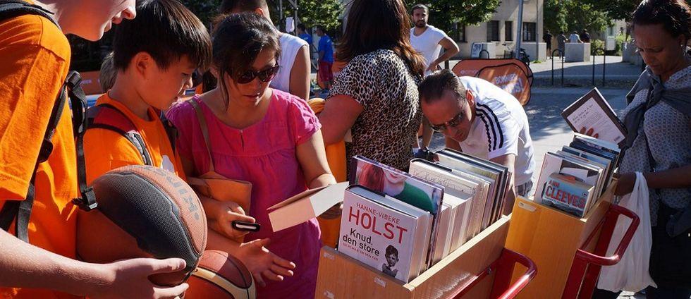 Barn och ungdomar spelar basket och läser böcker under en sommarlovssatsning.