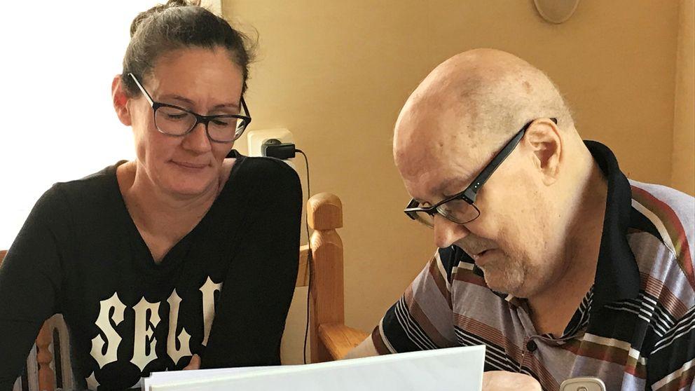 Kvinna och äldre man tittar i pärm