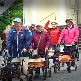 Äldre människor med rullatorer som går i kapp.