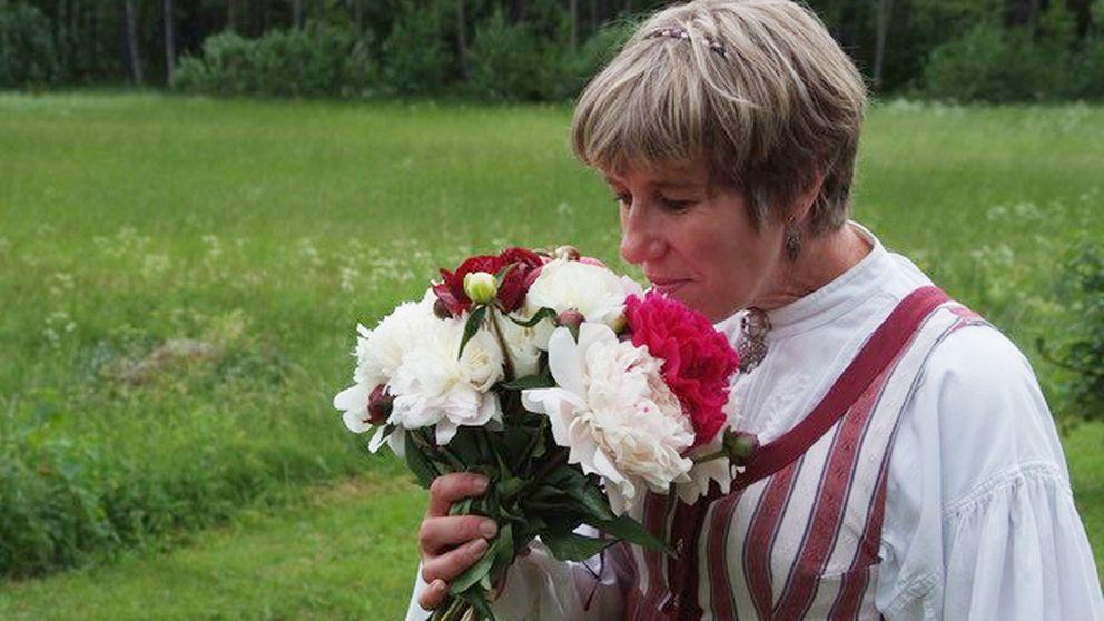 Doriz Zsiga iklädd folkdräkt luktar på en bukett med pioner.