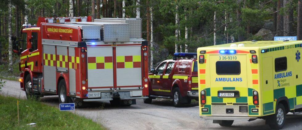 Ambulans och räddningstjänst står på en grusväg.