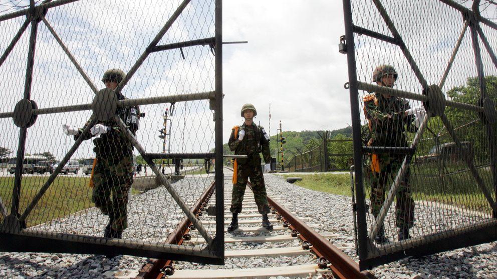 Sydkoreanska soldater öppnar en grind i den demilitariserade zonen för att släppa igenom ett nordkoreanskt tåg. Arkivbild.