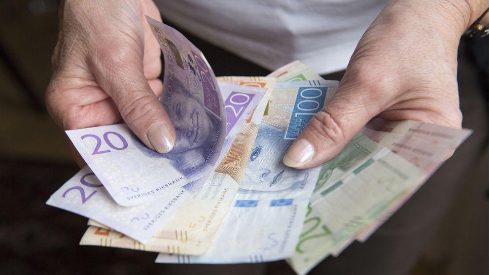 Håller pengar i handen.