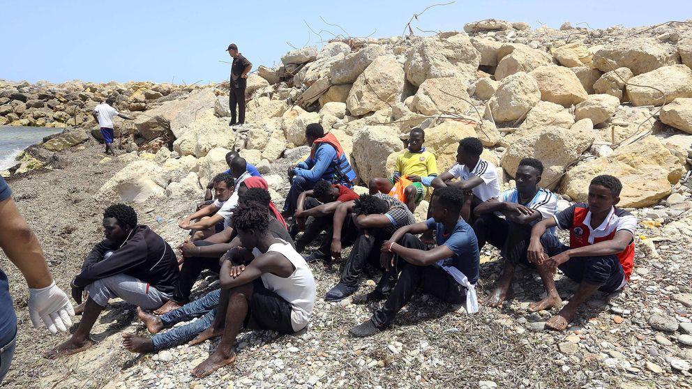 Migranter som räddades av den libyska kustbevakningen sitter på land öster om Tripoli.