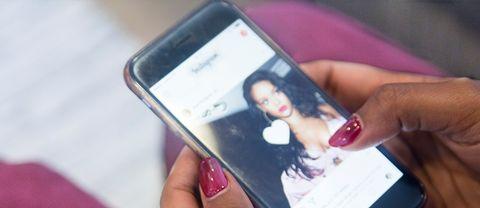 En ung kvinna kollar instagram på mobilen.