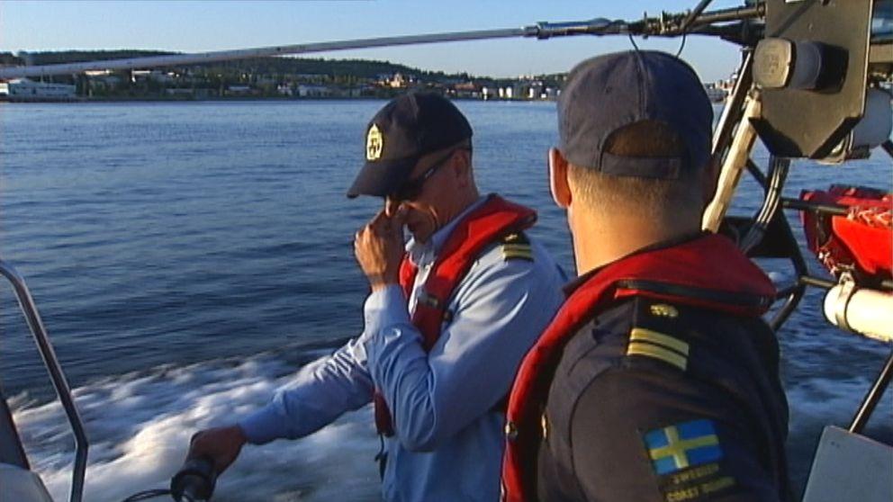 två tjänstemän som åker på kustbevakningens båt