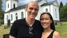 ett ungt, leende par står framför en kyrka